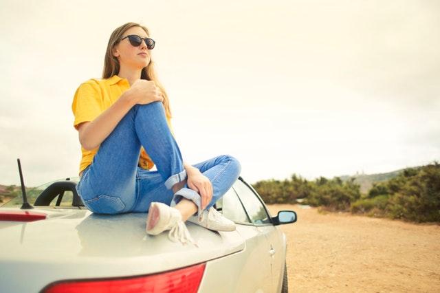Žena sediaca na striebornom aute