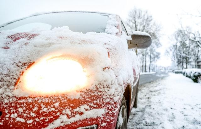 Červené zasnežené auto stojí na kraji cesty