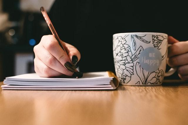 Žena so šálkou, ktorá píše do zošita