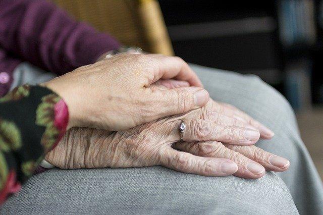 Dvaja starí ľudia sa držia za ruky.jpg